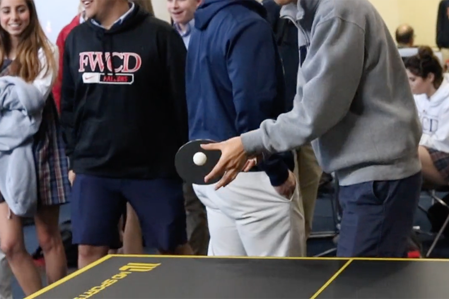 Jacon Sun '19 takes on US history teachers Quinton Davis and Sara Teegarden on the first day of ping pong in the commons.
