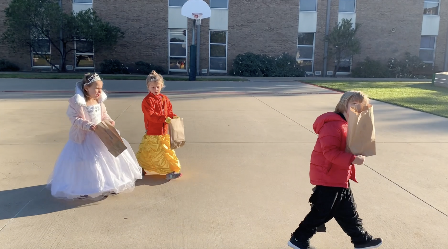Junior Kindergarten students walks by the Middle School on their way to trick-or-treat and sing in the Patton Field House