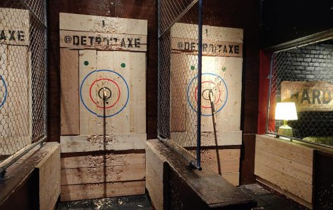 Axe throwers stand at the end of the stall and throw at the bullseye and the two blue dots above the rings, the